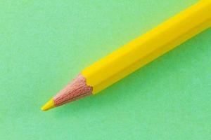 matita di colore giallo su carta di colore verde disposta in diagonale foto