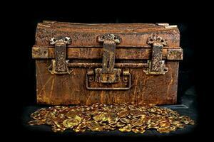 impilando moneta d'oro nella cassa del tesoro foto