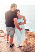 coppia incinta con le mani sulla pancia foto