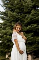 giovane donna incinta nella foresta foto