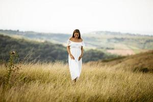 giovane donna incinta al campo foto