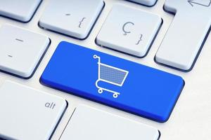 shopping online e-commerce concetto di acquisto di Internet icona del carrello sul tasto della tastiera blu foto