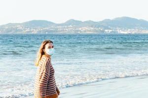 giovane donna che cammina sul mare in spiaggia con una mascherina chirurgica durante una giornata luminosa con un maglione messo e copia spazio foto