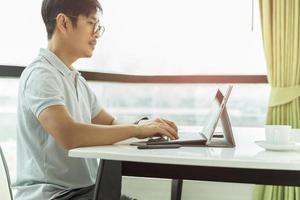 serio imprenditore concentrato o libero professionista in bicchieri e abiti casual che lavorano al computer portatile foto