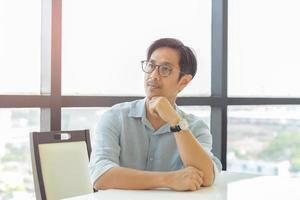 ritratto di uomo d'affari in occhiali da vista sedersi al tavolo appoggiato con la mano sul mento foto