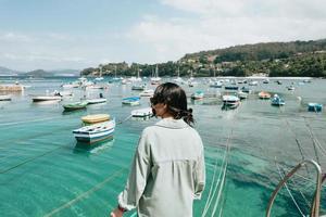 donna all'indietro di fronte al mare con molte barche durante una giornata di sole foto