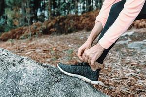 donna che lega i suoi lacci da tennis nella foresta foto