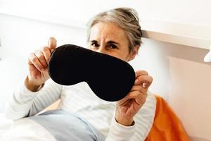 vecchia signora che mostra una maschera per dormire foto