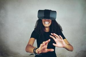 una giovane e bella donna nera con i capelli ricci afro indossa l'auricolare vr di realtà virtuale e gioca ai videogiochi mentre sorride in studio con sfondo grigio foto