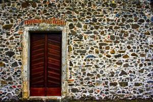 porta di legno sul muro di pietra pulito foto