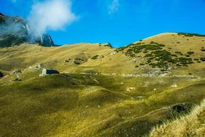 capanna tra i campi autunnali gialli su quello delle Alpi foto