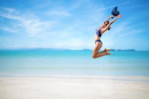 donna sexy in bikini blu che salta sulla spiaggia foto