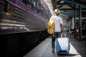 viaggiatore che cammina e attende il treno alla stazione ferroviaria foto