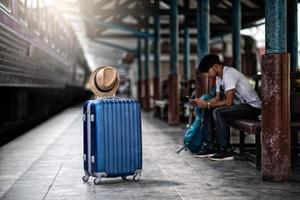 viaggiatore attende il treno alla stazione ferroviaria per viaggiare in estate foto