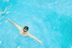 uomo in maschera subacquea nuota nell'oceano foto