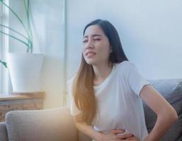 belle donne asiatiche seduta sul divano sta avendo crampi allo stomaco a causa delle mestruazioni foto