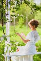 giovane sposa con capelli biondi in vestaglia bianca utilizzando profumo su un'altalena di corda foto