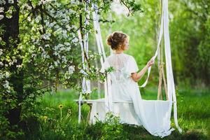 giovane sposa con capelli biondi in vestaglia bianca in posa su un'altalena di corda foto