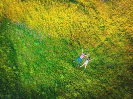 vista dall'alto di una coppia che pone insieme all'aperto felice nel campo estivo verde foto