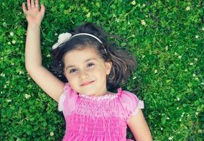 bambina che risiede nell'erba foto