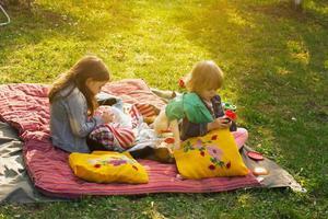 due bambine che hanno picnic nel cortile di casa foto