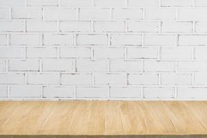 pavimento in legno con sfondo di muro di mattoni bianchi grunge foto