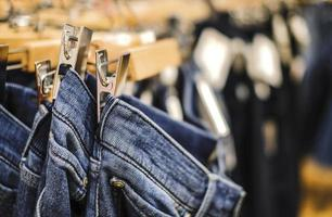 fila di pantaloni jeans blu impiccati in negozio foto