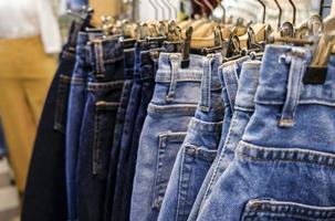 fila di gonne di jeans blu impiccati in negozio foto