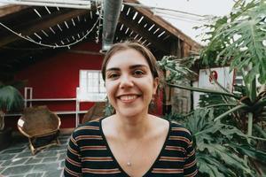 donna che sorride alla telecamera in un bar hipster durante una giornata luminosa foto