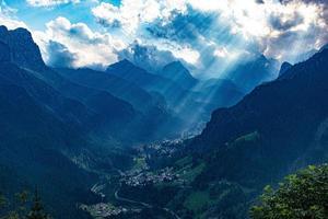 i raggi del sole illuminano la valle di alleghe foto
