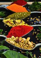 colorate varie erbe e spezie per cucinare su sfondo scuro foto