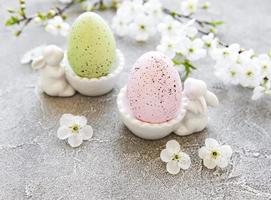 uova di Pasqua colorate in uno stand con figurine di coniglietto pasquale in ceramica e fiori primaverili su sfondo grigio cemento foto