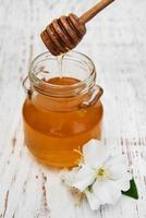 miele e fiori di gelsomino su uno sfondo di legno foto
