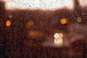 gocce d'acqua sulla finestra con luci sfocate tramonto dopo la pioggia foto