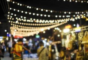 astratto sfondo sfocato di persone che fanno shopping al mercato notturno in città foto
