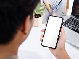 uomo che usa lo schermo vuoto di uno smartphone simula la scrivania bianca dell'ufficio foto