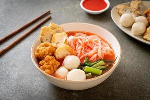piccoli spaghetti di riso piatti con polpette di pesce e polpette di gamberi in zuppa rosa, yen ta quattro o yen ta fo - stile asiatico foto