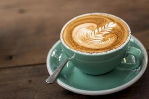 cappuccino caldo con latte art su fondo in legno foto