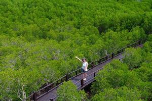 vista dall'alto di una giovane donna asiatica che cammina su un sentiero di legno nella foresta di mangrovie durante le vacanze estive foto