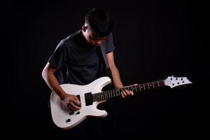 giovane in giacca di pelle nera con chitarra elettrica in studio foto