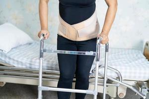 paziente signora asiatica che indossa cintura di supporto per il dolore alla schiena per lombare ortopedico con deambulatore foto
