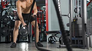 uomo che si allena con le corde da battaglia in palestra allenamento funzionale allenamento fitness sportivo foto