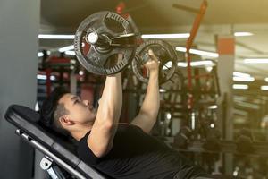 uomo sportivo che si allena con un bilanciere pesante foto