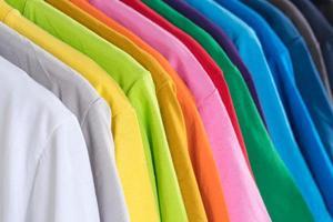 primo piano di magliette vestiti su grucce su sfondo bianco foto