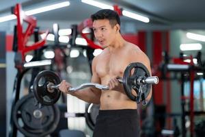 uomo sportivo che si allena con un bilanciere pesante in palestra foto