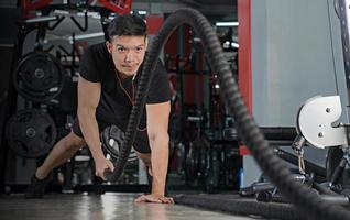 uomo che si allena con le corde da battaglia in palestra foto