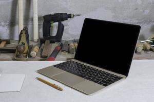 laptop in un laboratorio di falegnameria su un banco di lavoro e un trapano in background foto