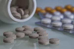 le pillole sono sparse sul tavolo del trattamento o del suicidio foto