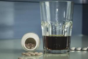 le pillole sono sparse sul tavolo whisky o rum trattamento o suicidio foto