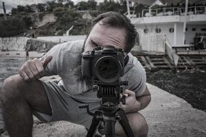 fotografo con macchina fotografica e treppiede foto